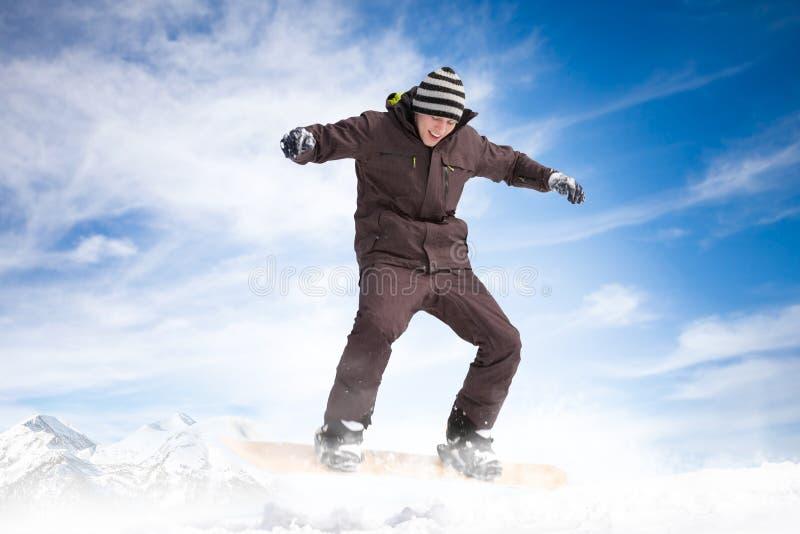 Snowboarder скача против голубого неба стоковые изображения rf