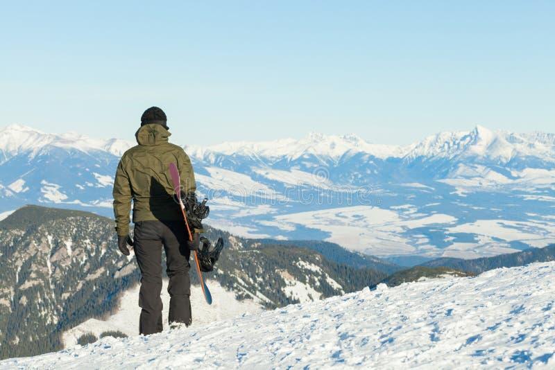 Snowboarder смотря красивый пейзаж от вершины горы стоковое фото