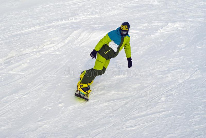 Snowboarder сползает вниз наклон на фоне снега стоковая фотография rf