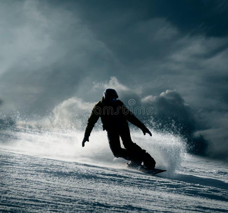 Snowboarder сползает вниз снежный холм стоковое изображение rf