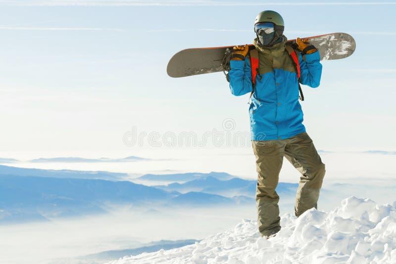 Snowboarder стоя вверху очень гора на золотом часе и держа сноуборд на его плечах стоковые фотографии rf