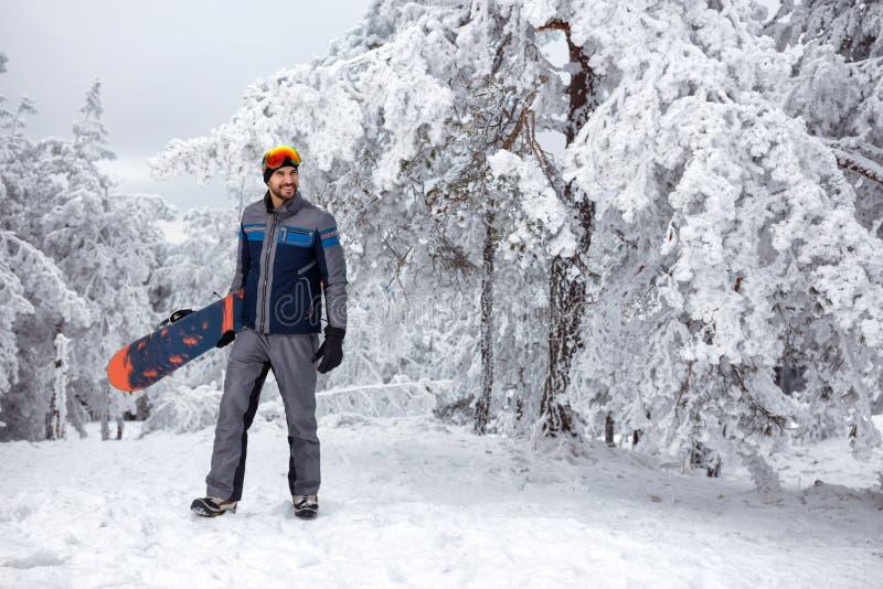 Snowboarder с сноубордом на зимнем отдыхе в горе стоковая фотография