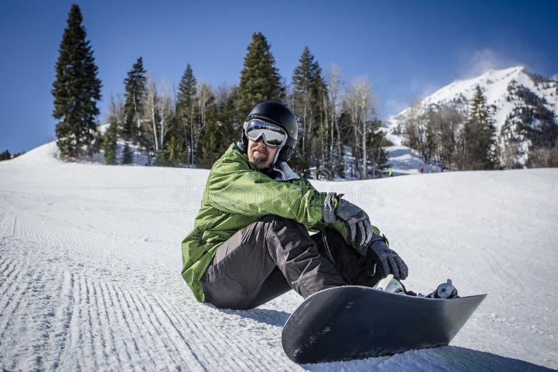 Snowboarder adulto masculino que descansa em um monte preparado da neve fotografia de stock