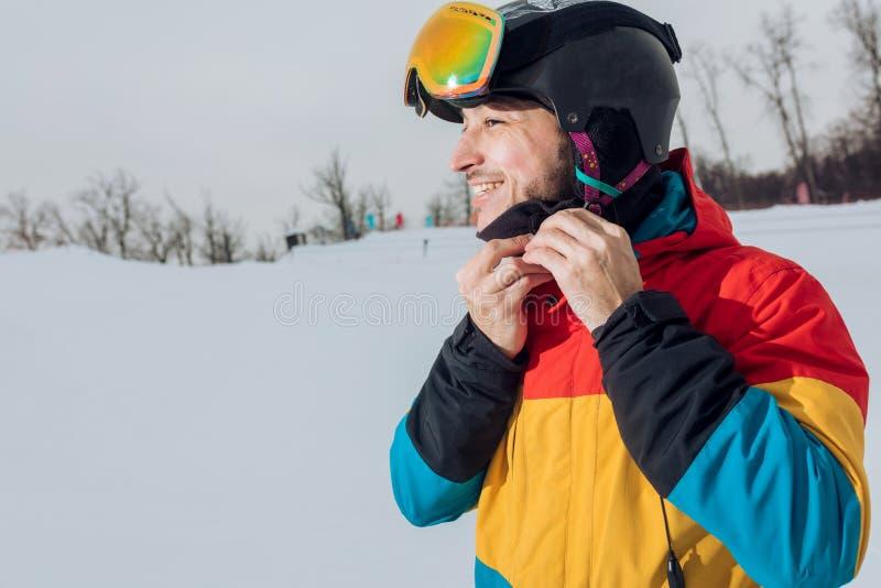 Snowboarder alegre joven que pone en su ropa de deportes imágenes de archivo libres de regalías