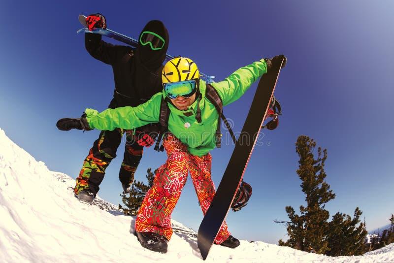 Snowboarder alegre que presenta encima de una montaña foto de archivo libre de regalías
