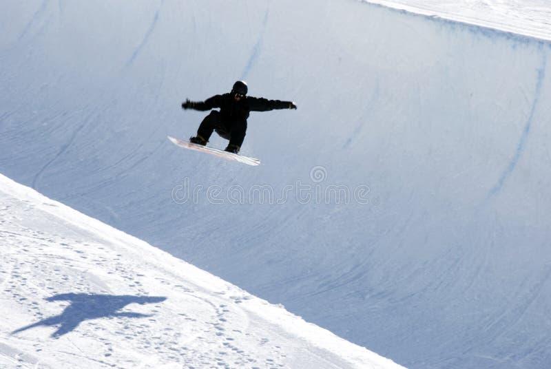 Snowboarder auf halber Rohrspur lizenzfreies stockfoto