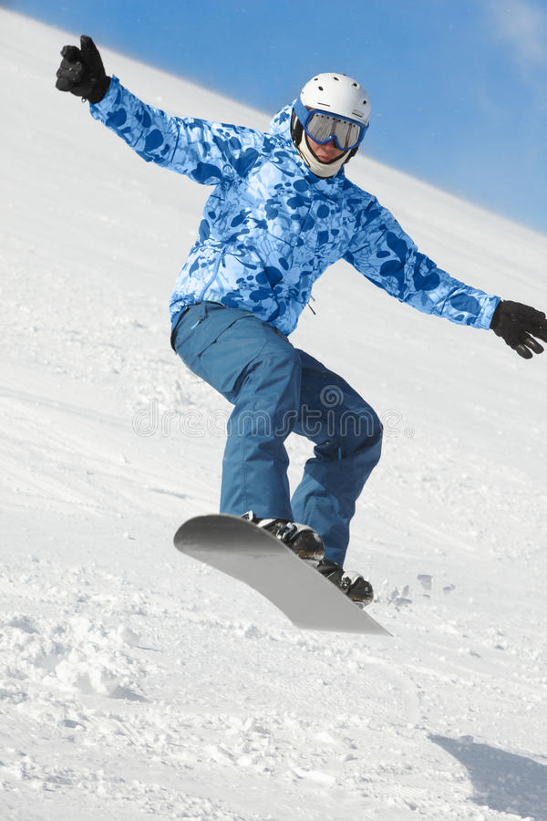 Snowboarder balances when flies on snowboard stock image