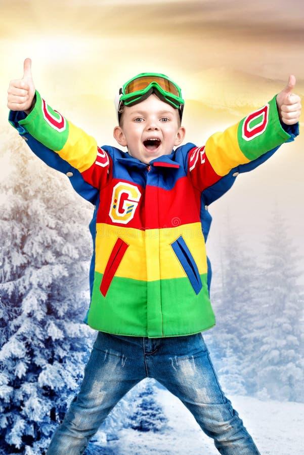 Snowboarder bello del ragazzo in giacca a vento luminosa nel legno nevoso di inverno immagini stock