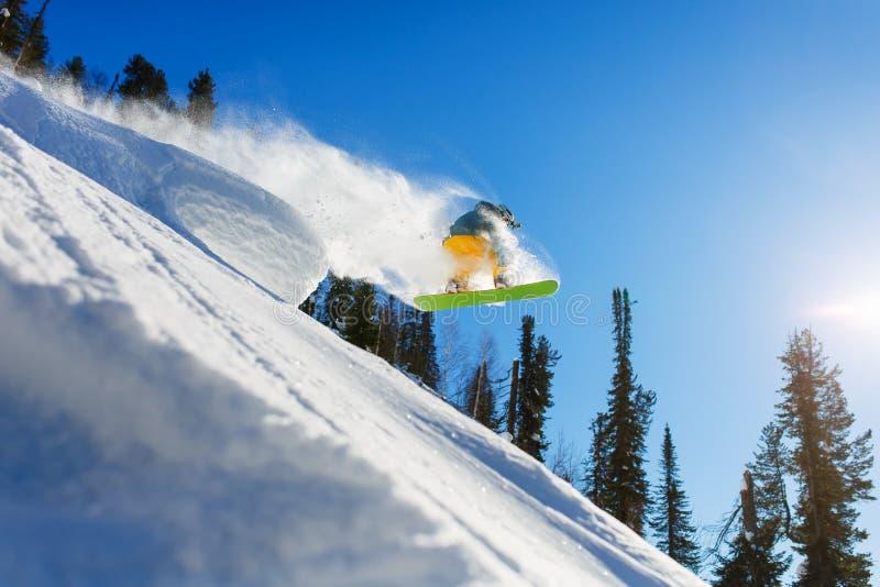 Snowboarder bij sprong inhigh bergen bij zonnige dag stock fotografie