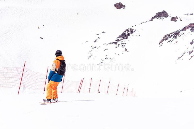 Snowboarder in a black helmet riding on a snowy track. Man learns to snowboarding rides over fresh snow on the slope in winter, ex stock photos