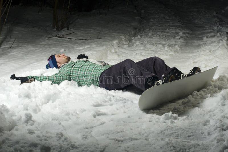Snowboarder che risiede nella neve fotografia stock libera da diritti