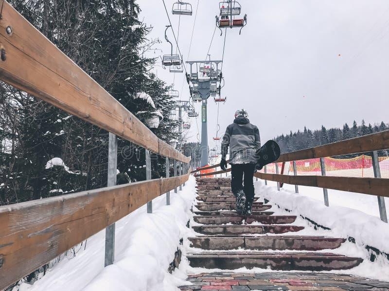 Snowboarder chodzi w górę schodków w narta raporcie Perspektywiczny widok obraz stock