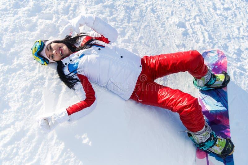 Snowboarder con lo snowboard in abiti sportivi fotografia stock libera da diritti