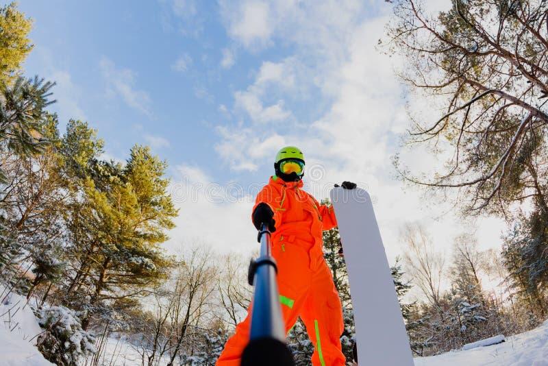 Snowboarder con lo snowboard che fa un selfie immagini stock libere da diritti
