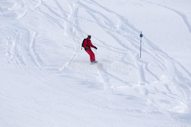 Snowboarder cuesta abajo en cuesta fuera de pista nevosa foto de archivo libre de regalías
