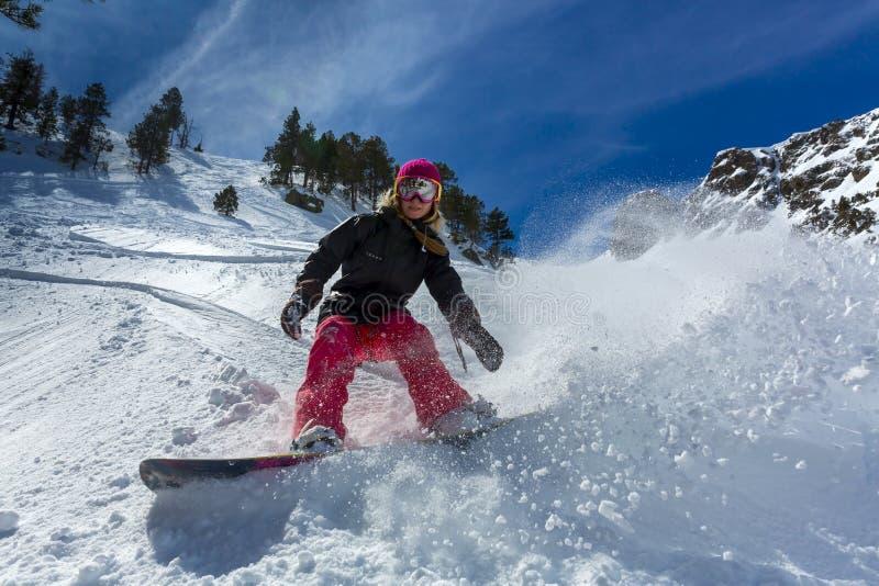 Snowboarder da mulher no movimento nas montanhas foto de stock