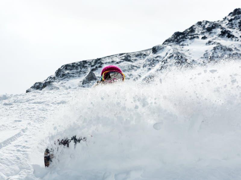 Snowboarder da mulher no movimento nas montanhas imagem de stock royalty free