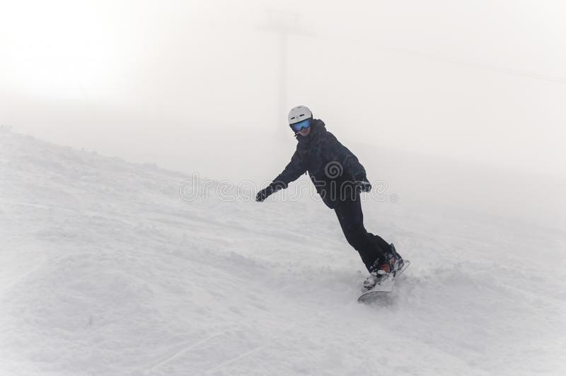 Snowboarder daalt van een hoge berg op een helling bij de winter koude dag royalty-vrije stock afbeeldingen
