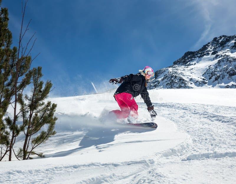 Snowboarder de la mujer en el movimiento en montañas imágenes de archivo libres de regalías