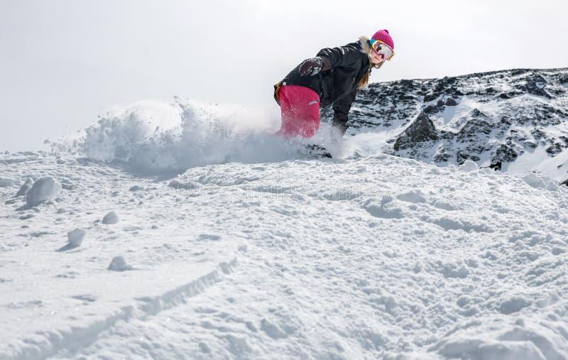 Snowboarder de la mujer en el movimiento en montañas fotografía de archivo libre de regalías