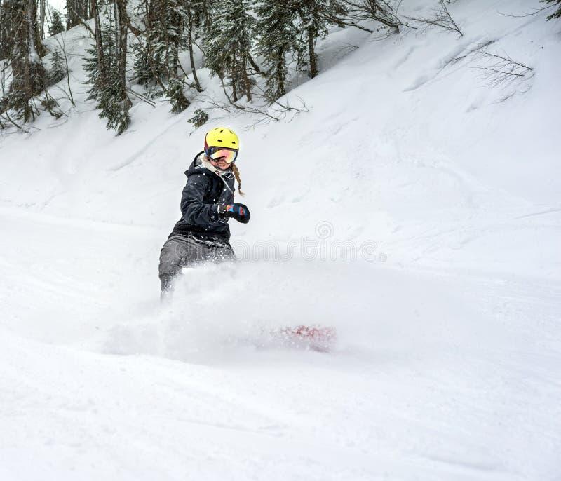 Snowboarder de la mujer en el movimiento en montañas fotos de archivo libres de regalías