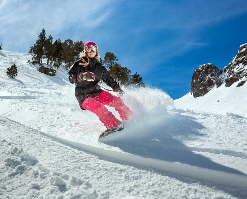 Snowboarder de la mujer en el movimiento en montañas imagen de archivo