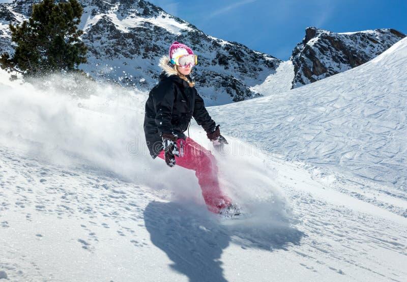 Snowboarder de la mujer en el movimiento en montañas fotos de archivo