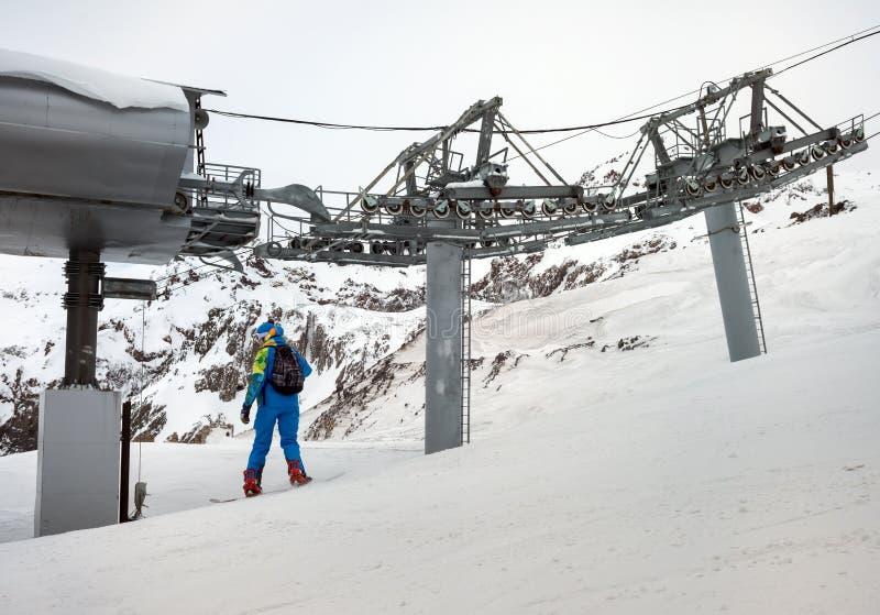 Snowboarder de la mujer en montañas fotos de archivo