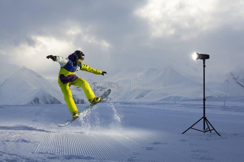 Snowboarder de Photoshoot que salta luz artificial do flash imagem de stock royalty free