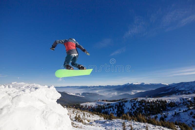 Snowboarder de salto en montañas en estación de esquí en el fondo Dragobrat del cielo azul imagenes de archivo