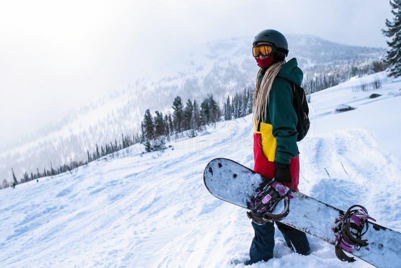 Snowboarder de sexo femenino parasitario con la snowboard en las montañas en una cuesta nevosa Deporte fotos de archivo