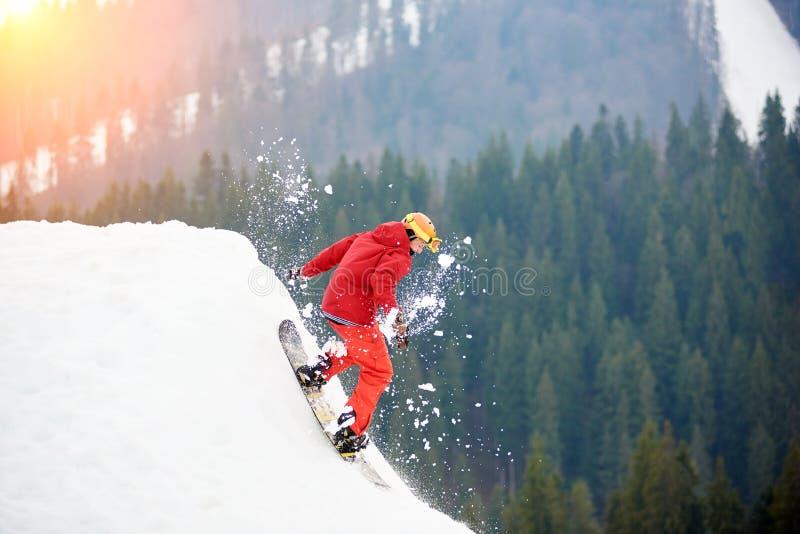 Snowboarder de sexo masculino en un montar a caballo rojo del traje desde arriba de la cuesta nevosa con la snowboard foto de archivo libre de regalías