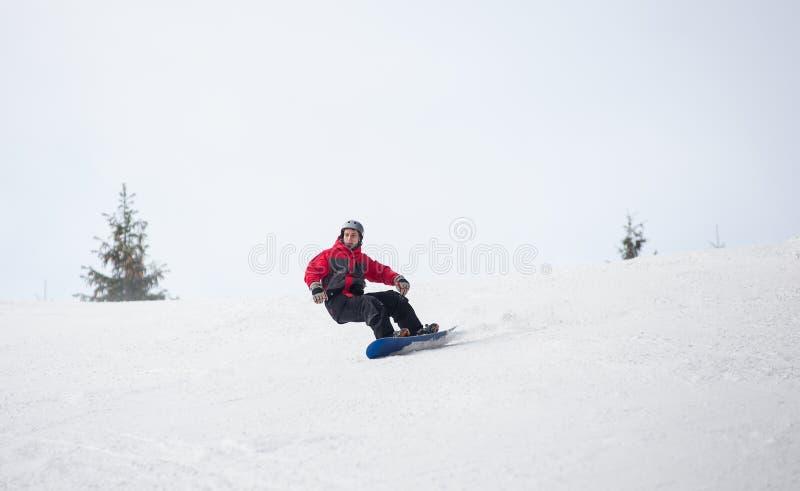 Snowboarder de sexo masculino que monta abajo de la montaña en día de invierno fotografía de archivo