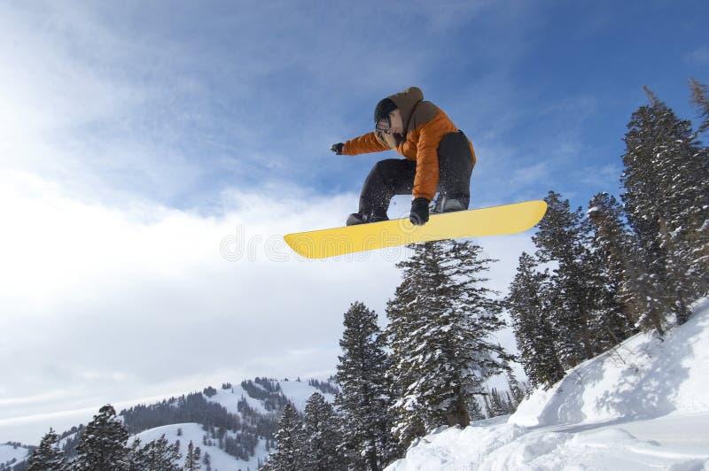 Snowboarder de sexo masculino que salta sobre la colina nevada imagen de archivo