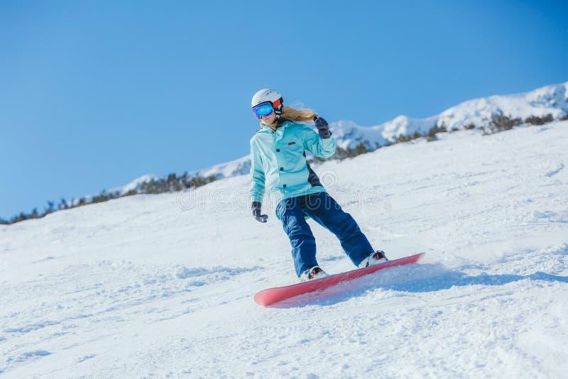 Snowboarder della donna nelle montagne fotografia stock