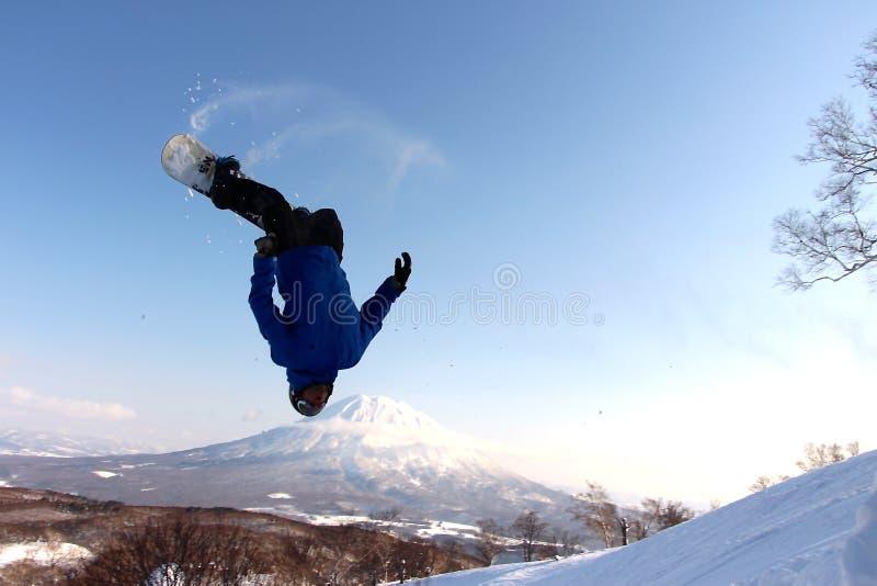 Snowboarder, der es weg vom backcountry Sprung sendet lizenzfreies stockfoto