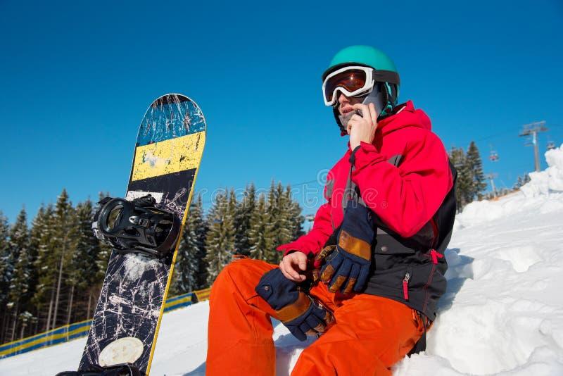 Snowboarder, der intelligentes Telefon in den Bergen verwendet lizenzfreies stockfoto