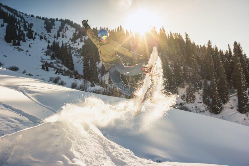 Snowboarder, der seine Trickmethode mit Nasenzupacken tut stockbild