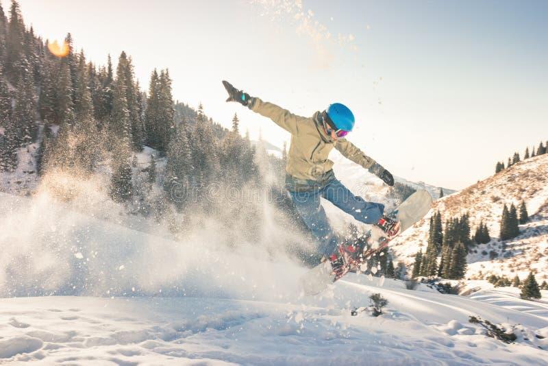 Snowboarder, der seine Trickmethode mit Nasenzupacken tut stockfoto