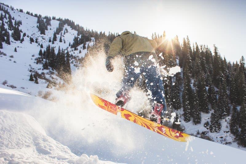 Snowboarder, der seinen Trick eine achtzig, Snowboardingwettbewerb tut stockfotografie