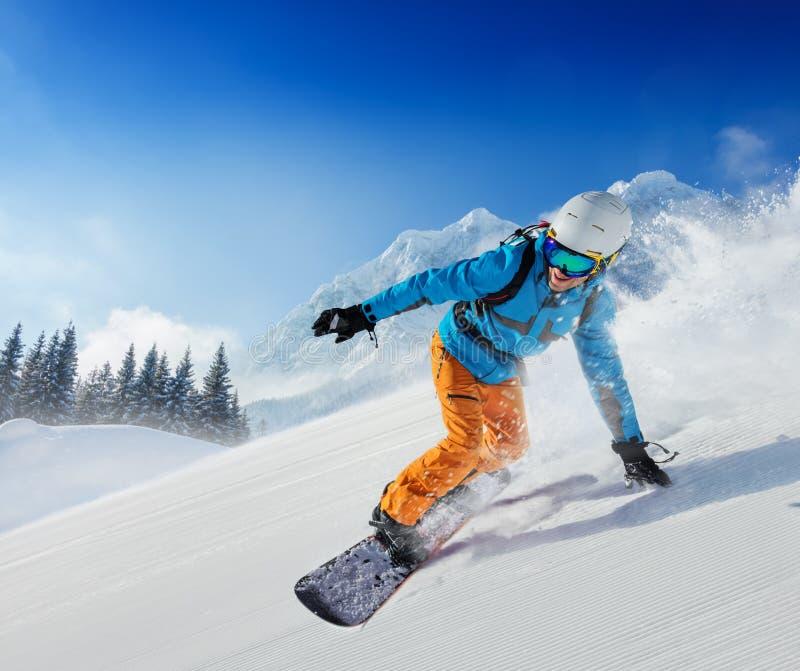 Snowboarder des jungen Mannes, der hinunter die Steigung in den alpinen Bergen läuft stockfoto