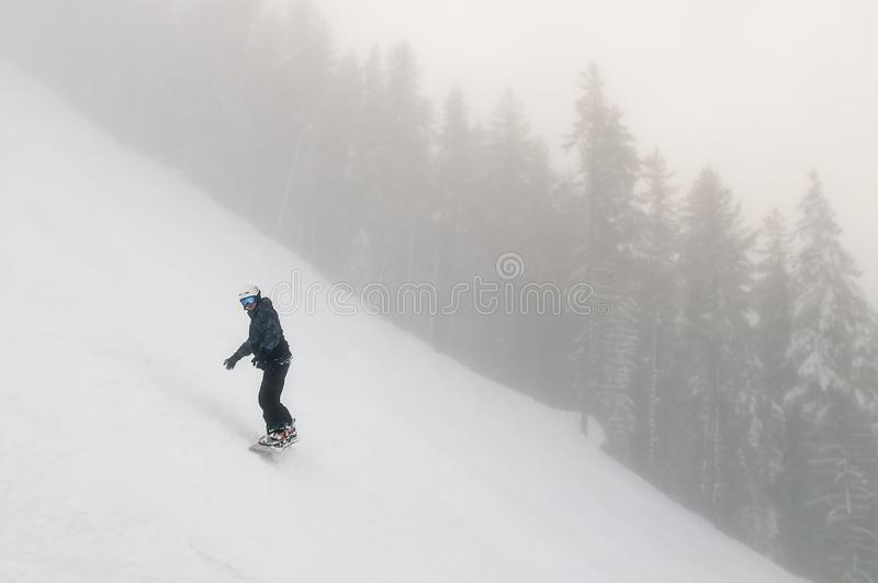 Snowboarder descends from a high mountain on a slope at winter cold day royalty free stock photography