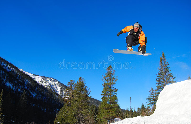 Snowboarder di Ornge che salta su fotografia stock libera da diritti