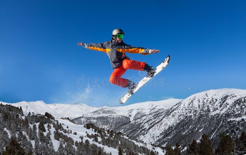 Snowboarder die hoog als ninja springen stock afbeelding