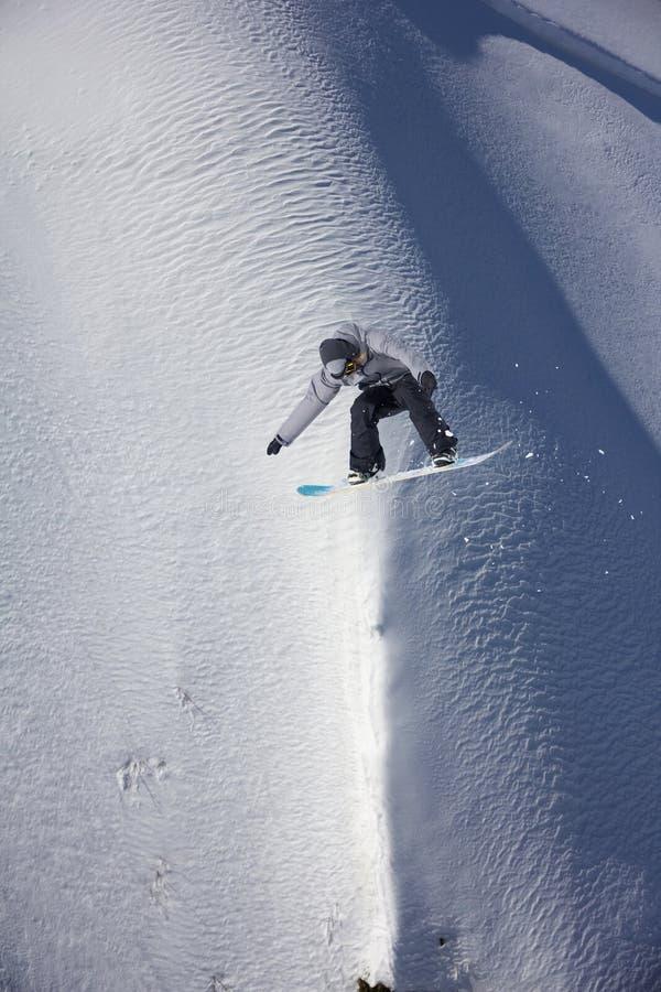 Snowboarder die op de achtergrond van sneeuwhelling vliegen Extreme wintersporten, het snowboarding stock foto