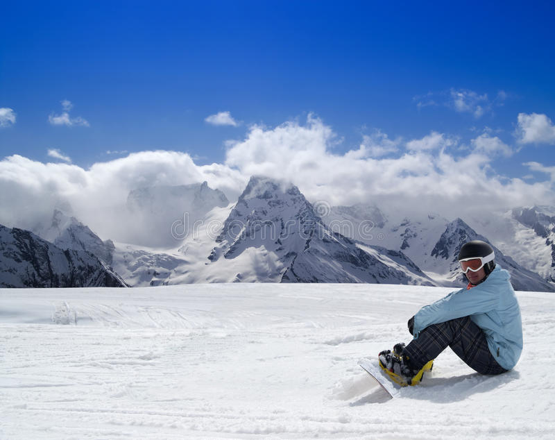 Snowboarder die op de skihelling rust stock fotografie