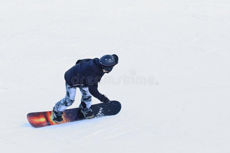 Snowboarder die op een snowboard onderaan de snow-covered helling bij een skitoevlucht berijden De sport van de winter Vrij slag  stock afbeeldingen