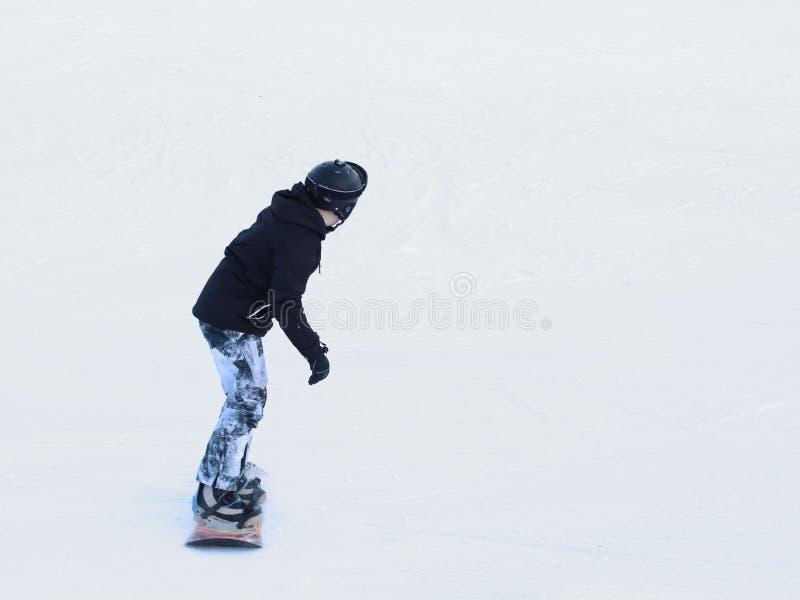 Snowboarder die op een snowboard onderaan de snow-covered helling bij een skitoevlucht berijden De sport van de winter Vrij slag  stock afbeelding