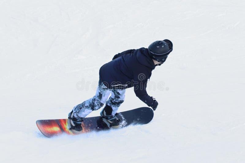 Snowboarder die op een snowboard onderaan de snow-covered helling bij een skitoevlucht berijden De sport van de winter Vrij slag  royalty-vrije stock fotografie