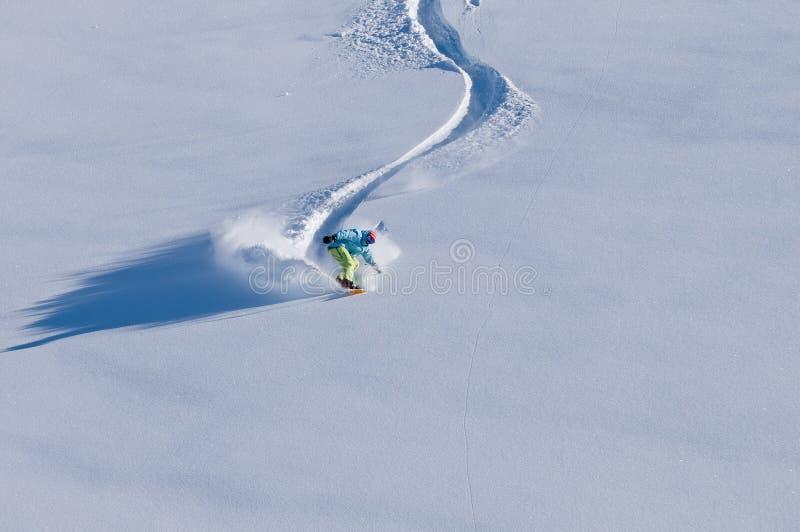 Snowboarder die pret in diepe backcountry sneeuw heeft royalty-vrije stock afbeelding
